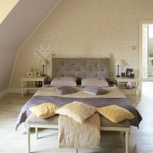 Delikatny wzór tapety stanowi doskonałe tło dla łóżka z wysokim, tapicerowanym zagłówkiem. Proj. Karolina Łuczyńska. Fot. Bartosz Jarosz.