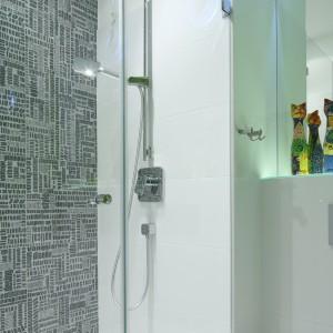 Całą łazienkę wyłożono białymi płytkami. Wyróżniona została tylko centralna ściana za prysznicem. Pokryto ja płytkami z nadrukiem przypominającymi strony gazet codziennych. Projekt Katarzyna Mikulska-Sękalska. Fot. Bartosz Jarosz.