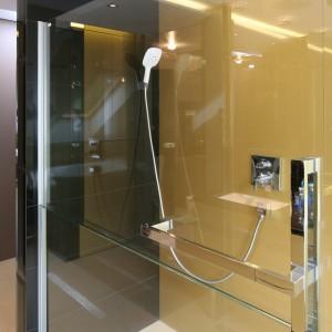 Ekskluzywny charakter przestrzeni wyznaczają eleganckie materiały wykończeniowe i wyposażenie. Ścina prysznica w złotym kolorze doskonale prezentują się w duecie z czarnymi błyszczącymi płytki na ścianie obok. Projekt Chantal Springer. Fot. Bartosz Jarosz.