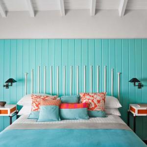 Turkusowy panel umieszczony za łóżkiem i nocnymi stolikami tworzy ciekawą dekorację. Fot. Luis Pons Design Lab.