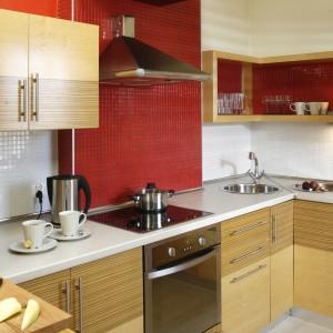 Ceramiczną mozaikę szkliwioną na kolor czerwony wybrano z oferty Ceramiki Paradyż. Meble wykonano z płyty w okleinach zebrano modyfikowane i klon. Projekt: InsideLab. Fot. Bartosz Jarosz.
