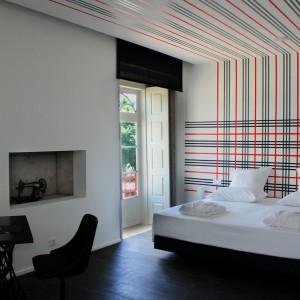 W tym pokoju na odbiorcę silnie wpływa grafika - linie umieszczone na ścianie i suficie łączą obie płaszczyzny tworząc spójną przestrzeń. Fot. Design & Wine Hotel.