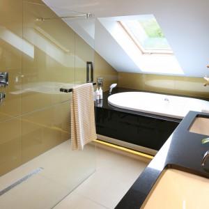 Poza dużą, wygodą wanną mieszczoną pod skosami, znalazło się w tej komfortowej łazience również miejsce na prysznic oraz saunę fińską – suchą i parową. Szklana tafla oddziela prysznic od części z umywalkami, funkcjonalnie dzieląc przestrzeń łazienki. Jest praktycznie niewidoczna, co pozwoliło wyeksponować szkło Lacobel w kolorze złota. Projekt Chantal Springer. Fot. Bartosz Jarosz.