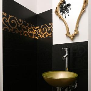 Szklana umywalka oraz rama lustra kupiona na targu staroci zostały pomalowane złotą farbą. Dzięki temu idealnie pasują do złoceń na czarnych płytkach, którymi wykończono wnękę prysznica. Projekt Magdalena Konochowicz. Fot. Bartosz Jarosz.