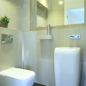 Utrzymana w ciepłych beżach nieduża toaleta udekorowana została złotem. W jego różnorodnych odcieniach są właściwie wszystkie ozdobne okładziny ścienne. Projekt Agnieszka Hajdas-Obajtek. Fot. Bartosz Jarosz.