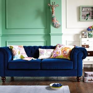 Jasne, kolorowe poduszki bardzo ładnie wyglądają na ciemnej kanapie. Fot. Debenhams.