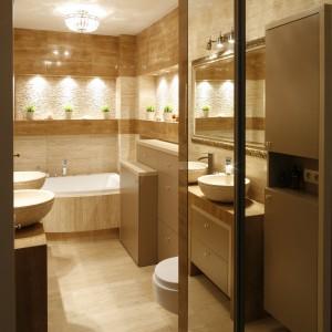 Lustrzana zabudowa tuż przy wejściu do łazienki nie tylko daje dodatkowe miejsce do przechowywania, ale też skrywa w sobie pralkę. Projekt Jolanta Kwilman. Fot. Bartosz Jarosz.