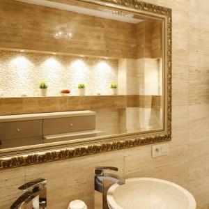 Duża tafla lustra tuż nad umywalkami została oprawiona w stylową, złotą ramę. To nie jedyny tak zdobny element dekoracyjny we wnętrzu. Projekt Jolanta Kwilman. Fot. Bartosz Jarosz.