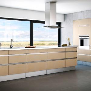 Meble z kolekcji Siena Sand z oferty firmy Nettoline. Drewniane fronty w ładnych, jasnym odcieniu ocieplają beton zastosowany na ścianach. Głównym elementem kuchni jest duża (3,5 metra) wyspa z widokiem na krajobraz za oknem.