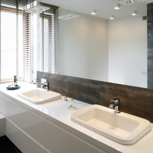W przestronnej łazience znajdują się dwie umywalki. Nad nimi umieszczono lustrzaną taflę, która optycznie powiększa przestrzeń. Proj. Agnieszka Ludwinowska. Fot.Bartosz Jarosz.