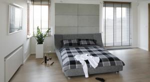 Przestronna sypialnia została urządzona w minimalistycznym stylu. W odpowiednich proporcjach połączono biel, drewno oraz szarość betonu.