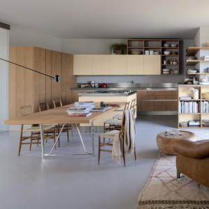 Meble z kolekcji Oysterdec firmy Veneta Cucine. Duża ilość szafek zapewnia sporo miejsca na przechowywanie. Kolor beżowy zastosowana na szafkach wiszących oraz na wyspie pięknie łączy się z drewnem.