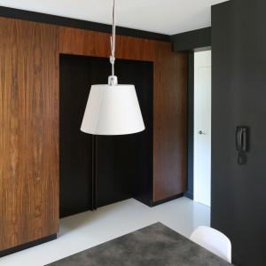 Drzwi przesuwne wykończone bejcowanym na czarno dębem oddzielają kuchnię od korytarza. Można je zamknąć lub pozostawić otwarte, gdy jest taka potrzeba. Projekt: Kasia i Michał Dudko. Fot. Bartosz Jarosz.