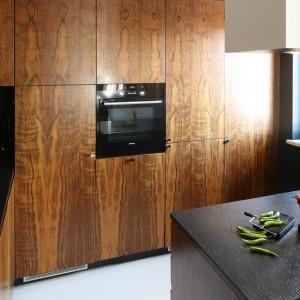 Fronty wykończone fornirem drewna egzotycznego amazoue otwierają się w większości bez pomocy tradycyjnych uchwytów. Wyjątkiem są szafki ze sprzętami AGD, do których dobrano stylowe, galwanizowane gałki. Projekt: Kasia i Michał Dudko. Fot. Bartosz Jarosz.