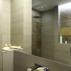 Zamontowana tuż nad umywalką duża tafla lustra optycznie powiększa niewielką przestrzeń łazienki. Projekt Piotr Stanisz. Fot. Bartosz Jarosz.