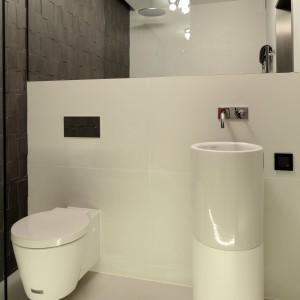Przestrzeń niewielkiej łazienki organizuje klarowny podział na strefę WC z umywalką oraz umiejscowiona na przeciw nich kabinę prysznicową. Efekt czystości aranżacji podkreśla wszechobecna biel. Projekt Justyna Smolec. Fot. Bartosz Jarosz.