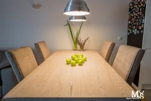 Proekologiczne wnętrze z wykorzystaniem naturalnych materiałów: drewno, cegła, szkło. Stół z ciekawym usłojeniem, krzesła w kolorach ziemi, roślinność oraz industrialne oświetlenie tworzą wyjątkowy nastrój pomieszczeń.