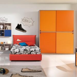 Pomysłowa aranżacja przestrzeni chłopca z wykorzystaniem pomarańczowej szafy oraz półek i czerwonego łóżka. Fot. Giessegi.