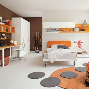 Pomarańczowy dywan i elementy mebli ożywiają biało-brązowe wnętrze. Fot. Colombini Casa.