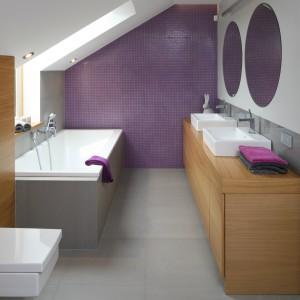 Łazienka jest kolorystyczną kontynuacją sypialni. Szarości połączono z fioletem a całość ocieplono drewnianymi elementami. Proj. Małgorzata Galewska. Fot. Bartosz Jarosz