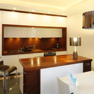 W kuchni królują dwa materiały – biały, lakierowany MDF, z którego wykonana jest zabudowa oraz drewno. Blaty wykonane zostały z deski parkietowej z drewna merbau. Ścianę pomiędzy szafkami wykończono natomiast płytą meblową fornirowaną merbau. Projekt: Agnieszka Żyła. Fot. Bartosz Jarosz.