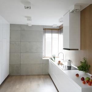 Biel i płytki z surowego betonu architektonicznego, którymi wyłożona jest jedna ze ścian, ociepla płyta meblowa w kolorze naturalnego dębu. Pięknie wyeksponowano na niej białą prostą bryłę okapu. Projekt: Agnieszka Ludwinowska. Fot. Bartosz Jarosz.