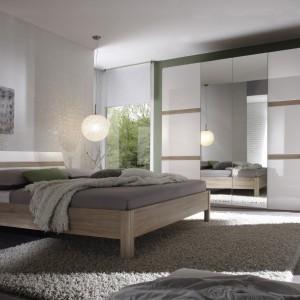 """Kolekcja mebli Selene to nowoczesny zestaw mebli do sypialni. Połączenie jasnych frontów z białym połyskiem oraz dekoru """"Dąb Sonoma"""". Fot. Helvetia Meble Wieruszów."""