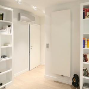 Biały grzejnik płytowy umieszczony jest obok szafy. Dzięki czemu kompozycyjnie nie odbiega od pozostałego wystroju. Proj. Nasciturus design. Fot. Bartosz Jarosz.