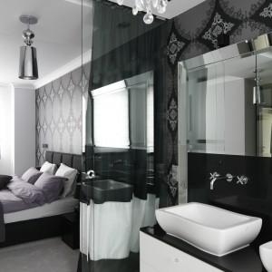Łazienka jest kontynuacją stylu panującego w sypialni. Biel i czerń przełamano szarościami. Ozdobne oświetlenie dodaje wnętrzu uroku. Proj. Magdalena Smyk. Fot. Bartosz Jarosz.