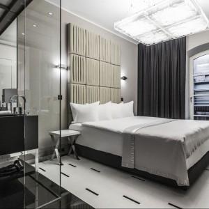 Strefa łazienki została optycznie oddzielona od sypialni za pomocą szklanych ścinek i ciemnej podłogi. Fot. Blow up hotel, Poznań.