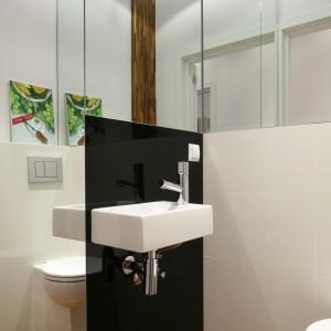 Toaleta dla gości jest elegancka i reprezentacyjna, ale także ciepła i stylowa. Białe płytki w dużym formacie i czarne szkło zestawiono z drewnem - na podłodze parkiet przemysłowym. Proj. Katarzyna Merta- Korzniakow. Fot. Bartosz Jarosz