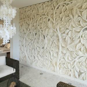Sprowadzony z Bali ręcznie wykonany relief z piaskowca z motywem kwiatów lotosu zdobi całą ścianę. Pierwotnie był jedną, olbrzymią taflą. Do transportu pocięto ją na bloki.  Grubość reliefu to ok. 20 cm, co daje niesamowite efekty, kiedy go podświetlimy. Inaczej prezentuje się w sztucznym świetle, a jeszcze inaczej w słońcu i o różnych porach dnia. Projekt: Karolina Łuczyńska. Fot. Bartosz Jarosz.