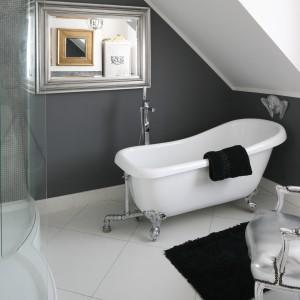 Obok wanna na stylowych chromowanych nóżkach ustawiono fotel ze srebrną tapicerką, który zaprasza do relaksu po kąpieli. Projekt: Magdalena Konochowicz. Fot. Bartosz Jarosz.