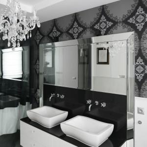 W tej łazience połączonej z sypialnią wykorzystano biel i czerń.  Tapeta z barokowym wzorem i piękne lustra wykończone szeroką fazą prezentują się wytwornie. Projekt: Magdalena Smyk. Fot. Bartosz Jarosz.