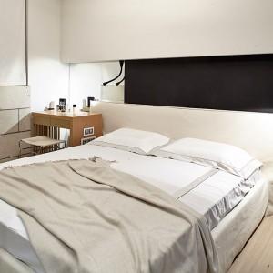 Sypialni nadano przytulny charakter. Podłogę wykończono drewnianą okładziną w naturalnym, jasnym odcieniu drewna. Na fragmencie ściany okładzina z płytek w odcieniu beżu. Fot. Olga Akulova DESIGN.