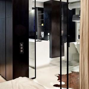 Przeszklone drzwi umownie dzielą i łączą sypialnię z przestrzenią dzienną. Intymność zapewnia zasuwana zasłona, dopasowana kolorystycznie do aranżacji wnętrza pomieszczenia. Fot. Olga Akulova DESIGN.