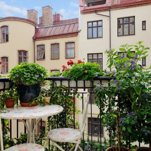 Zielony balkon - kwiaty umieszczone na balkonowej balustradzie, donice stojące na podłodze tworzą przestrzeń w której przyjemnie się odpoczywa. Fot. Alvhem Makleri.