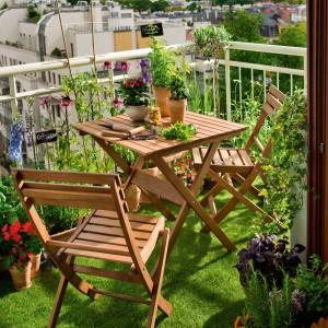 Dzięki donicom, kwiatom oraz sztucznej trawie nawet niewielki balkon możemy zamienić w mini ogródek. Na balkonie dobrze sprawdzą się składane meble. Na zdjęciu meble Worchester wykonane z drewna eukaliptusowego w kolorze  naturalnego drewna. Fot. Castorama.