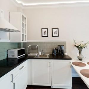 W mieszkaniu dominują delikatne stonowane kolory, tylko gdzieniegdzie urozmaicone mocniejszym akcentem. Zdecydowanie są nim czarno-grafitowe blaty w kuchni, kontrastujące z białymi meblami. Fot. Sun & Snow