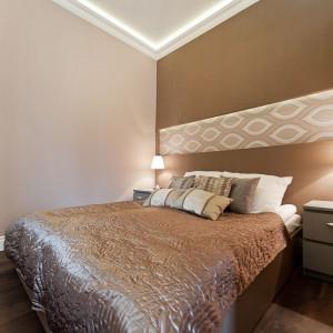 W obrębie sypialni dominują ciepłe barwy, beże, brązy, odcienie czekolady. Ściana za zagłówkiem łóżka została pomalowana na ciemniejszy kolor, dopasowany do kolory łóżkowej narzuty.  Fot. Sun & Snow