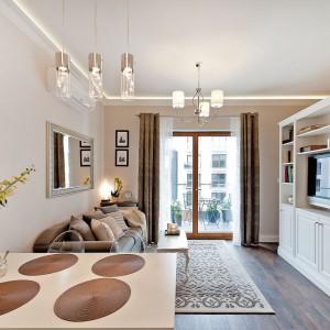 Podłogi w całym mieszkaniu pokryto drewnianymi panelami w ciemnym odcieniu mahoniowym - sprawdź. Fot. Sun & Snow