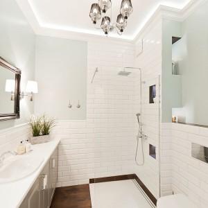"""Łazienka zamienia się w ekskluzywny salon kąpielowy, dzięki wykończeniu podłóg naturalnym, ciemnym drewnem. Szklane ścianki kabiny prysznicowej są prawie niewidoczne, optycznie nie zabierając nic z przestrzeni pomieszczenia, a umiejętne schowanie pralki w ciągu szafek zapobiega efektowi """"rupieciarni"""", często spotykanym w niewielkich łazienkach. Fot. Sun & Snow"""