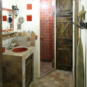 Idealnym tłem dla wyjątkowej aranżacji łazienki są płytki z antycznej cegły. Wykonano z nich posadzkę, okładzinę ścienną, a także wykończono bryłę szafki podumywalkowej. Projekt: Dorota i Michał Ługowoj. Fot. Bartosz Jarosz