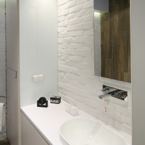 Surowa powierzchnia cegieł  wprowadza do łazienki loftowy klimat. Na tle cegieł świetnie wygląda podtynkowa bateria praz lustro bez ramy.  Projekt: Dominik Respondek. Fot. Bartosz Jarosz