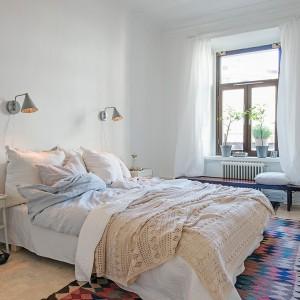 Spokojną kompozycję ocieplają miękkie tkaniny oraz kolorowy, wzorzysty dywan. Fot. Alvhem Mäkleri.