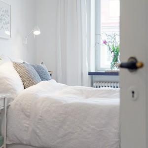 Białe ściany w połączeniu z tkaninami w delikatnych odcieniach pozwolą nam stworzyć przytulną, spokojną sypialnię. Fot. Alvhem Mäkleri.