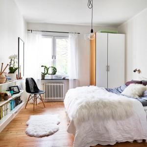 Białe ściany w sypialni stanowią doskonałe tło dla kolorowych dodatków. Drewniana podłoga ociepla przestrzeń sypialni. Fot. Stadshem.