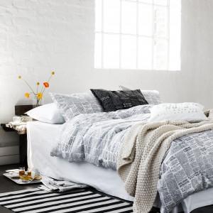 Biel potrafi wyeksponować kolory tkanin. W zestawieniu z ciemna podłogą tworzy przyjemny kontrast. Fot. H&M Home.