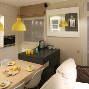 Nowoczesny salon w klimacie surowych wnętrz skandynawskich jest chłodny, a jednocześnie przytulny. Wszystko to dzięki żółtym jak słońce dodatkom i prostocie wyposażenia. Projekt Lucyna Kołodziejska. Fot. Bartosz Jarosz.
