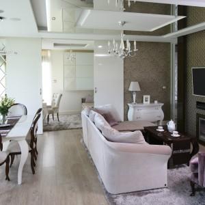 """Salon zachwyca różnorodnością użytych materiałów, struktur i kolorów. Wszystko jednak zostało podane w dobrze wyważonych proporcjach.  Już od progu wnętrze czaruje klasyczną elegancją i luksusem. Zachwyca blaskiem i niezwykłą pałacową wytwornością. Imponuje ilością dekoracyjnych wykończeń, struktur. A jednak niczego nie ma tu w nadmiarze. Wszystkiemu nadano odpowiednie proporcje. Dominujące we wnętrzu szkło i błyszczące wykończenia ocieplają bardziej """"miękkie"""" materiały – tapety, dywany i tapicerki na ścianach oraz drewno. Porywający efekt zapewniają trójwymiarowe płytki w kolorze starego złota. Projekt Agnieszka Hajdas-Obajtek. Fot. Bartosz Jarosz."""